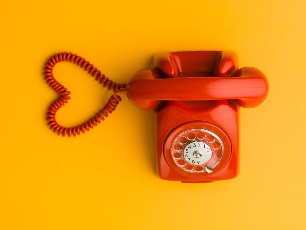 39045069 - upper view of red phone with heart shape made out of its cable, on yellow background